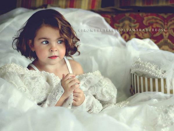 Klein meisje in trouwjurk van mama